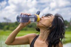 A garrafa de água potável chinesa asiática desportiva saudável nova da mulher após o treinamento da aptidão e o corredor malham f imagem de stock