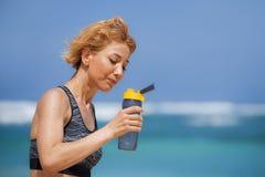 Garrafa de água potável feliz e atrativa nova da mulher do corredor do esporte ou bebida isotonic após ter corrido o exercício no imagem de stock royalty free