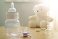 Garrafa de bebê, chupeta e brinquedo de um bebê Fotografia de Stock