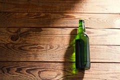 Garrafa de cerveja em uma tabela de madeira Vista superior Foco seletivo Zombaria acima Copie o espaço molde blank fotografia de stock