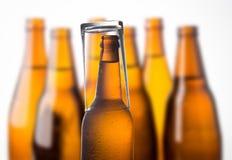 Garrafa de cerveja fria empilhada no fundo branco Fotos de Stock Royalty Free