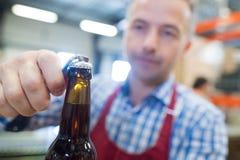 Garrafa de cerveja masculina da abertura do close up fotografia de stock royalty free