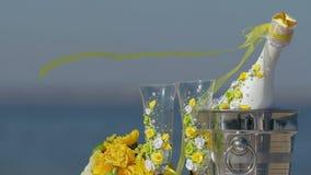 Garrafa de Champagne na cubeta de gelo, nos dois vidros e na decoração do casamento na praia vídeos de arquivo