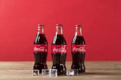 Garrafa de Coca-Cola com os cubos de gelo no fundo de madeira foto de stock