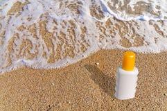 Garrafa de creme da proteção solar na praia Fotos de Stock Royalty Free