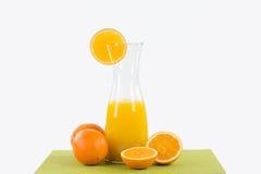 Garrafa de cristal grande con el zumo de naranja en un corredor de la tabla verde, deco Fotos de archivo libres de regalías