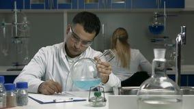 Garrafa de exame do cientista masculino com líquido no laboratório filme