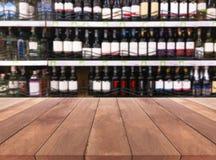 A garrafa de madeira do licor da tabela e do vinho na prateleira borrou o fundo Imagens de Stock