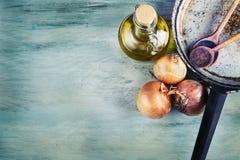 Garrafa de madera de las cebollas de la cuchara tres de la cacerola vieja de la cocina con aceite de oliva en la tabla de madera Fotos de archivo libres de regalías