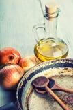Garrafa de madera de las cebollas de la cuchara tres de la cacerola vieja de la cocina con aceite de oliva en la tabla de madera Imagenes de archivo