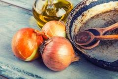 Garrafa de madera de las cebollas de la cuchara tres de la cacerola vieja de la cocina con aceite de oliva en la tabla de madera Imágenes de archivo libres de regalías