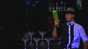 A garrafa de mnanipulação do barman masculino e faz o cocktail A mostra do empregado de bar, tiros claros, equipa o barman profis filme