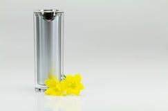 Garrafa de perfume com as flores amarelas no fundo branco Imagem de Stock