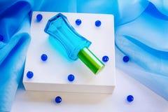 Garrafa de perfume de vidro azul e grânulos de vidro Foto de Stock Royalty Free