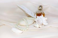 Garrafa de perfume do vintage com pérolas, marisco, pedra do mar branco e pena Foto de Stock Royalty Free
