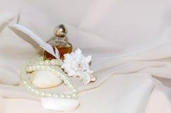 Garrafa de perfume do vintage com pérolas, marisco, pedra do mar branco e pena Imagens de Stock Royalty Free