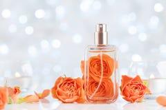 Garrafa de perfume e flores cor-de-rosa na tabela branca contra o bokeh Fundo da beleza e da perfumaria Fotografia de Stock Royalty Free