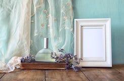 Garrafa de perfume fresca do vintage ao lado das flores aromáticas e quadro vazio antigo na tabela de madeira imagem filtrada ret Fotografia de Stock