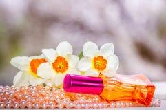 Garrafa de perfume, grânulos da pérola e flores de vidro vermelhos do narciso amarelo Fotos de Stock