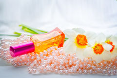 Garrafa de perfume, grânulos da pérola e flores de vidro vermelhos do narciso amarelo Fotografia de Stock Royalty Free