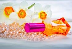 Garrafa de perfume, grânulos da pérola e flores de vidro vermelhos do narciso amarelo Imagens de Stock