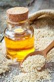 Garrafa de sementes de sésamo do óleo no saco na tabela de madeira velha fotografia de stock
