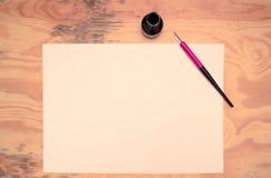 Garrafa de tinta, pena, papel, mesa de madeira Imagens de Stock Royalty Free