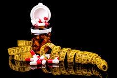 Garrafa de vidro com comprimidos da dieta e a fita de medição foto de stock