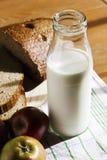 Garrafa de vidro com leite, pão preto e maçãs em uma tabela de madeira Imagem de Stock