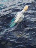 Garrafa de vidro com letra no mar Foto de Stock Royalty Free