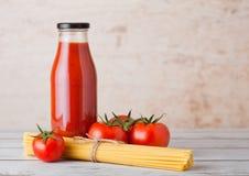 Garrafa de vidro da pasta de tomate com espaguetes crus Imagens de Stock Royalty Free