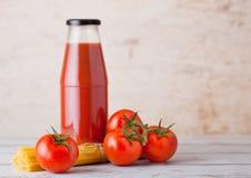 Garrafa de vidro da pasta de tomate com espaguetes crus Fotos de Stock