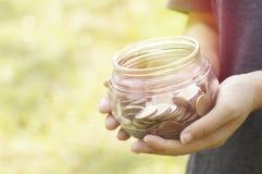 Garrafa de vidro da posse da moça das moedas para salvar o dinheiro e o conceito da doação Fotografia de Stock