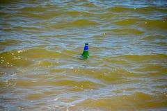 Garrafa de vidro que flutua na água do mar do oceano fotos de stock royalty free