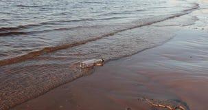 A garrafa de vidro vazia lava as ondas do mar na noite filme