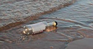 A garrafa de vidro vazia lava as ondas do mar na noite video estoque