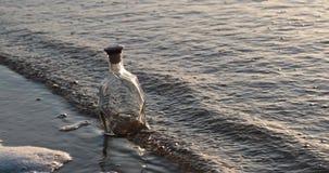 A garrafa de vidro vazia lava as ondas do mar na noite vídeos de arquivo