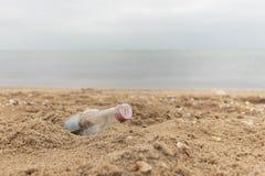 Garrafa de vidro vazia na areia Lixo na praia Costa de mar Poluição ambiental foto de stock