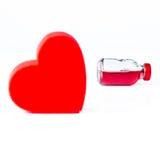 Garrafa de vidro vermelha e o coração na parte dianteira Fotos de Stock Royalty Free