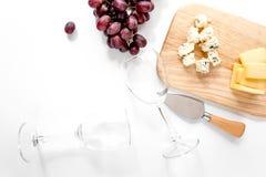 Garrafa de vidros do vinho tinto e de vinho com o queijo e a uva aperitive na opinião superior do copyspace branco do fundo Fotos de Stock Royalty Free