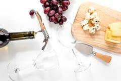 Garrafa de vidros do vinho tinto e de vinho com o queijo e a uva aperitive na opinião superior do fundo branco Foto de Stock