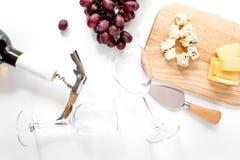 Garrafa de vidros do vinho tinto e de vinho com o queijo e a uva aperitive na opinião superior do fundo branco Fotografia de Stock
