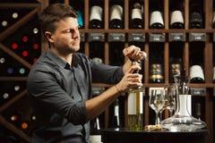 Garrafa de vinho branco de abertura do Sommelier com corckcrew fotografia de stock