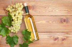 Garrafa de vinho branco e grupo das uvas brancas foto de stock