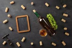 Garrafa de vinho branco, grupo de uvas, copo de vinho com corti?a, corkscrew e placa de giz no fundo preto foto de stock