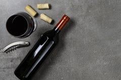 Garrafa de vinho, copo, cortiça e abridor no fundo concreto Copie o espa?o imagens de stock