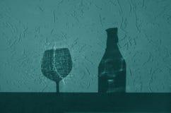 Garrafa de vinho e sombra de vidro no tom ciano imagem de stock royalty free