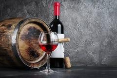 Garrafa de vinho tinto com vidro para provar e tambor de madeira na adega escura foto de stock