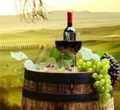 A garrafa de vinho tinto e o vidro de vinho wodden sobre o tambor Tusca bonito imagem de stock royalty free