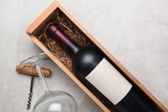 Garrafa de vinho tinto no caso de madeira com vidros e corkscrew Imagem de Stock